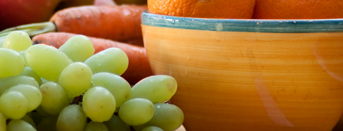 A close up photo of grapes next to a bowl