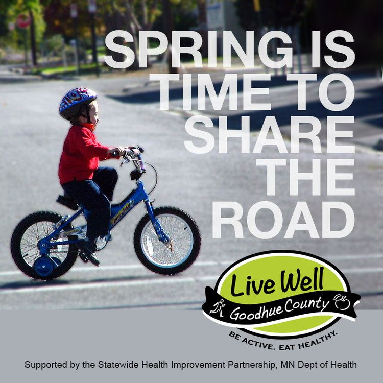 A boy riding a bicycle with text over the image that reads Spring is Time to Share the Road